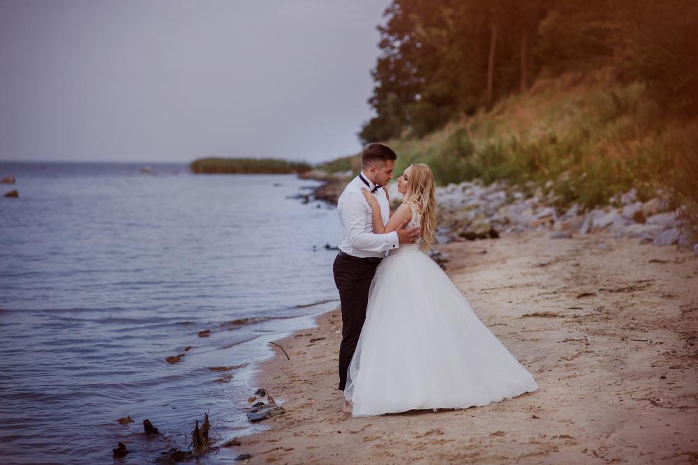 fotografia pary młodej w objęciach nad brzegiem
