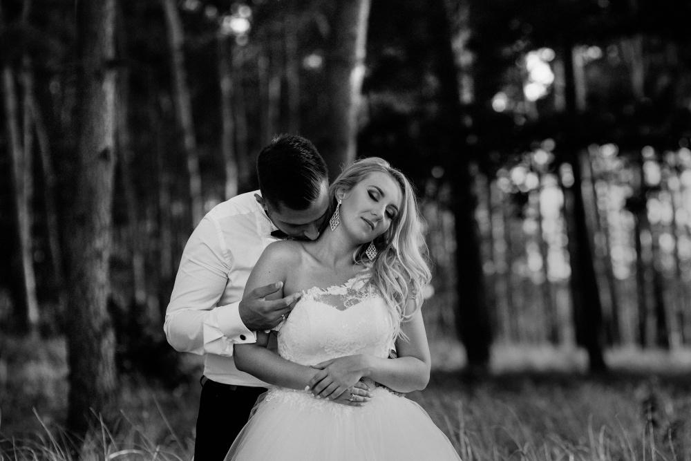 czarno-biała fotografia nowożeńców na tle lasu